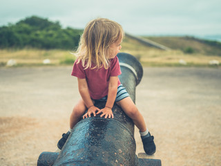 Little toddler sitting on a canon
