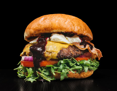 Craft burger is cooking on black background. Consist: sauce, arugula, tomato, onion, bacon, currant sauce, ricotta cheese, air bun and marble meat.