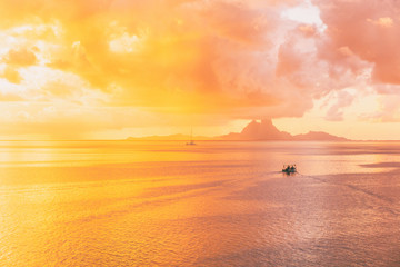 Tahiti sunset idyllic reflections of the sun setting over the ocean with yellow glowing colors in the sky and pink clouds in French Polynesia. Bora Bora island far away.