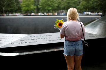 A woman holds a bouquet of flowers as she stands at the edge of the north reflecting pool at the 911 Memorial and Museum in New York