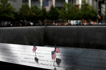 American flags are seen left at the edge of south reflecting pool at the 911 Memorial and Museum in New York