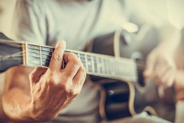 A man plays the guitar close-up. Toned photo.