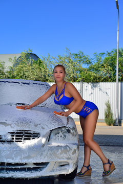 Girl in a swimsuit washes the car at the car wash