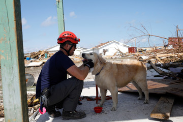 A member of the Canadian Burnaby Firefighters Search & Rescue Task Force pampers his dog during a search for the dead operation in the destroyed the Mudd neighbourhood after Hurricane Dorian hit the Abaco Islands in Marsh Harbour