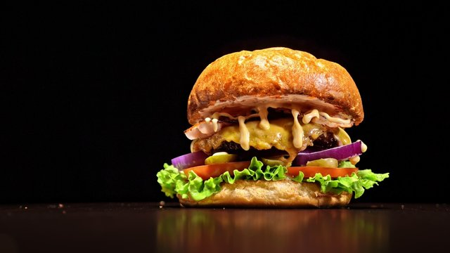 Craft burger is cooking on black background. Consist: sauce, lettuce, tomato, red onion, pickle, cheese, bacon, air bun and marbled meat beef.