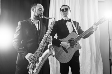 Group of two musicians, male jazz band, guitarist and saxophonist in classical costumes improvise on musical instruments in a studio black and white shot