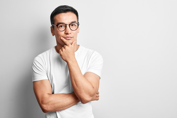 Smart Kazakh dressed in casuals and glasses thinks and doubts, holds his chin with hand on white studio background. Responsible Asian makes a decision