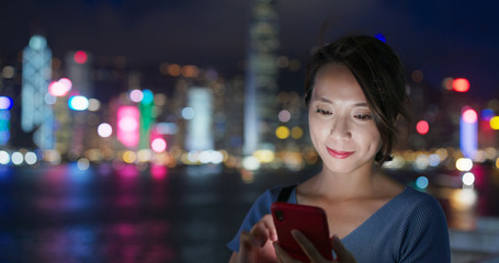 Wall Mural - Woman use of mobile phone in city of Hong Kong at night