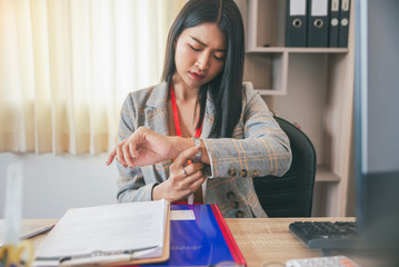 Professional Business woman seeing wrist watch to check time at office.Asian Businesswoman look at...