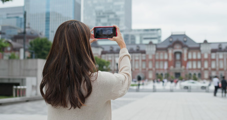 Woman take photo on cellphone in Tokyo station