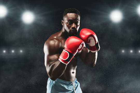 Confident african boxer standing in pose and ready to fight
