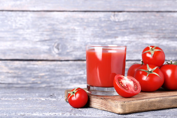 Wall Mural - Tomato juice in glass on grey wooden table