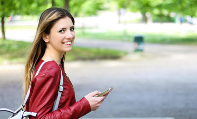 Woman walking in a park while using her smartphone