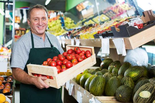 Man seller demonstraiting red tomatos