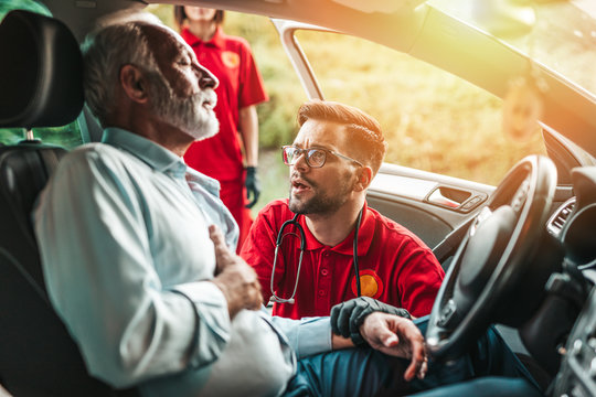 Elegant senior man with heart attack symptoms on the road. Emergency medical service workers trying to help him. Driver assistance service.