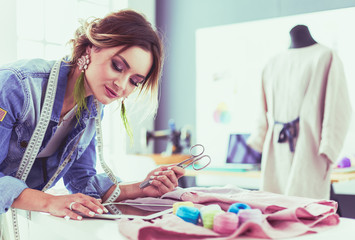 Fashion designer woman working with ipad on her designs in the studio