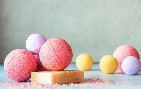 Colorful bath bombs, handmade soap and salt on the table, grey background, copy space. Home spa concept.