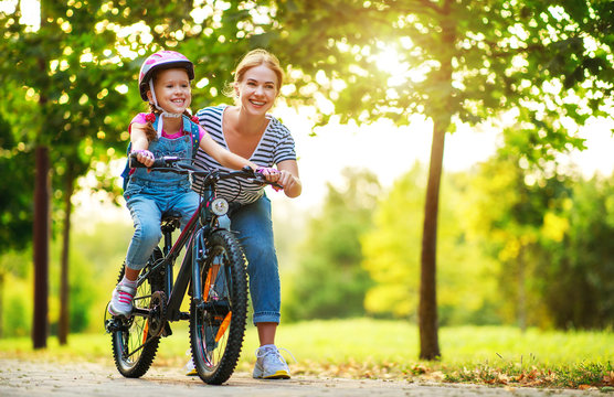happy family mother teaches child daughter to ride a bike in the Park