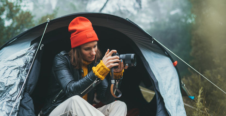 Wall Mural - photographer girl hold in hands mobile phone taking photo on smartphone autumn foggy mountain, tourist shooting on photo camera on background landscape, internet online concept