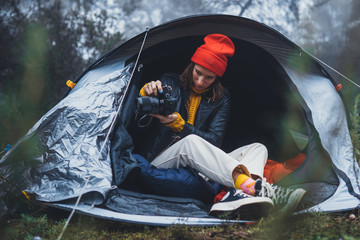Wall Mural - photographer tourist traveler take photo on camera in camp tent in foggy rain forest, hiker woman shooting mist nature trip, rest vacation concept camping holiday