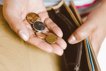 Woman holding empty wallet with some coins in her hand - Concept of economic crisis - Saving money for financial accounting.