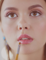 Beautiful girl with cosmetic powder brush for make up. Makeup. Make-up applying for perfect skin