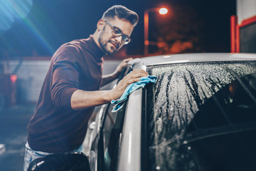 Young man washing his car in the evening at car wash station.
