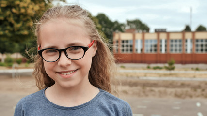 Portrait of a young smiling 11 year old girl with glasses.
