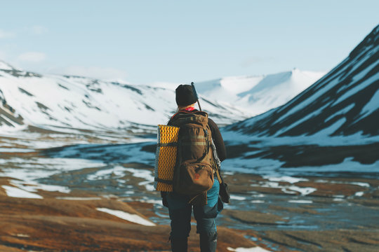 Rear view of hiker standing against snowcapped mountain