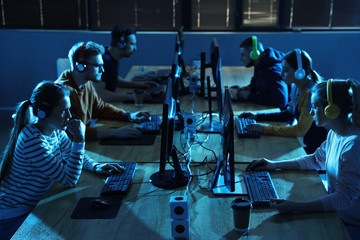 Group of people playing video games in internet cafe