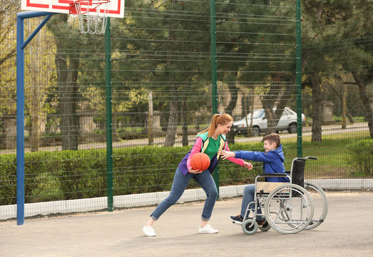 Preteen boy in wheelchair and young woman playing basketball on sports ground