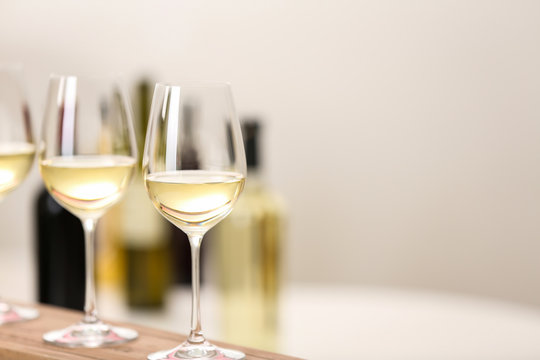 Glasses of wine on wooden board, space for text