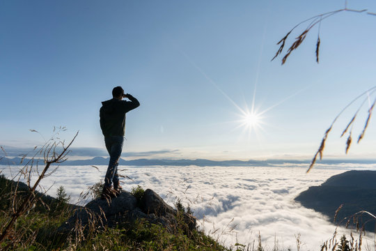 hiker standing on the top of a mountain and enjoying an amazing view over a cloud covered valley. Luck happiness and freedom concept in South Tyrol Italy
