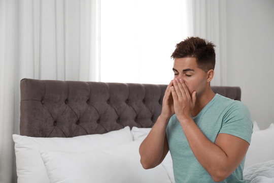 Young man suffering from allergy in bedroom