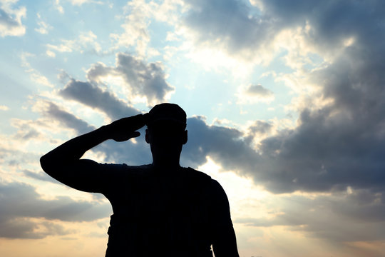 Soldier in uniform saluting outdoors. Military service