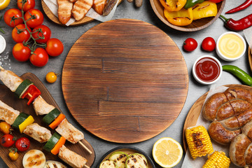 Flat lay composition with barbecued meat and vegetables on grey table. Space for text