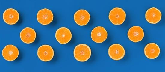 Foto op Canvas Vruchten Fruit pattern of fresh orange tangerine or mandarin on blue background. Flat lay, top view. Pop art design, creative summer concept. Citrus in minimal style.