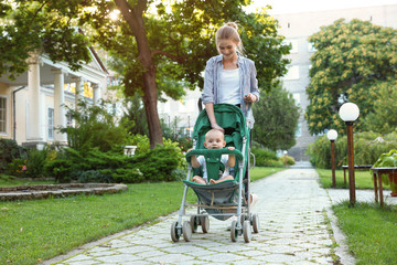 Teen nanny with cute baby in stroller walking in park. Space for text