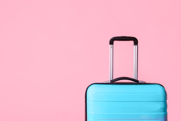 Modern blue suitcase on light pink background. Space for text Fototapete