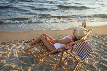 Young woman relaxing in deck chair on beach Fototapete