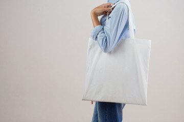 young woman holding eco cotton bag on white background