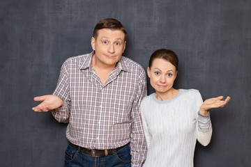 Portrait of puzzled couple shrugging shoulders and silly smiling