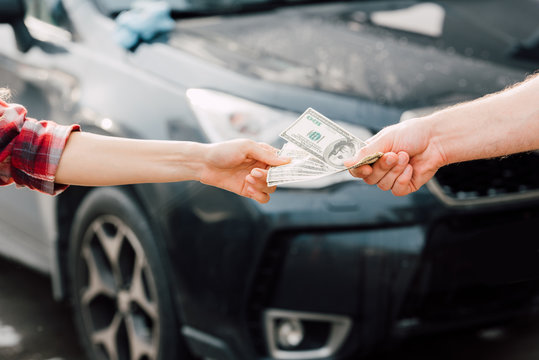 cropped view of man giving money to woman near car
