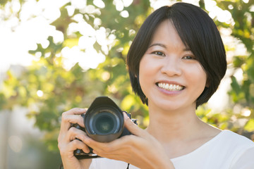 Portrait young Asian woman outdoor with a digital camera smiling