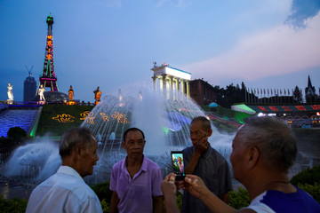 "Chinese men take pictures in front of a miniature replica of the Eiffel tower at a theme park called ""Window Of The World"" in Shenzhen"