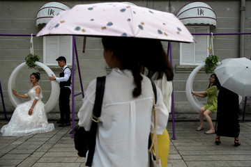 """A couple poses for their wedding photo at a theme park called """"Window Of The World"""" in Shenzhen"""