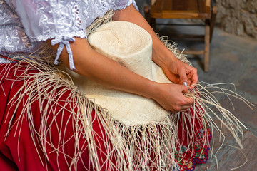 Woman weaving a Panama hat, also known as the traditional brimmed straw hat made of the Toquilla palm, which is on the Unesco Intangible Cultural list and famous from the city of Cuenca, Ecuador.