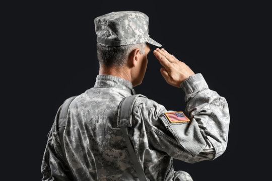 Saluting male soldier on dark background
