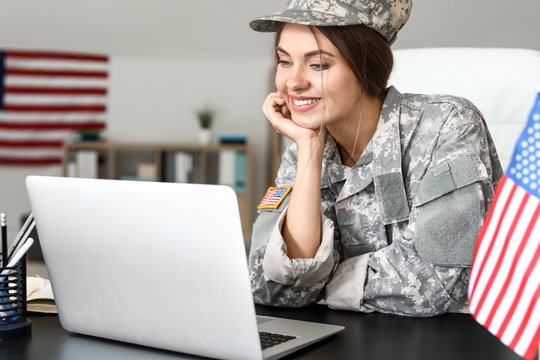 Young female soldier working with laptop in headquarters building