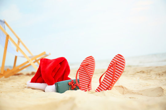 Santa Claus hat with gift box and flip-flops on sea coast. Christmas vacation
